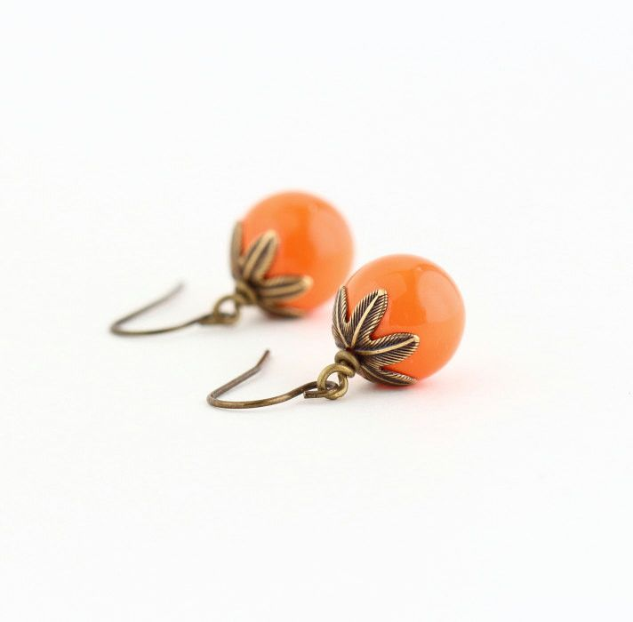 Vibrant orange beaded earrings with brass petal bead caps. These eye-catching beaded earrings feature opaque lively orange round glass beads topped with etched brass petal bead caps. The ear wires are