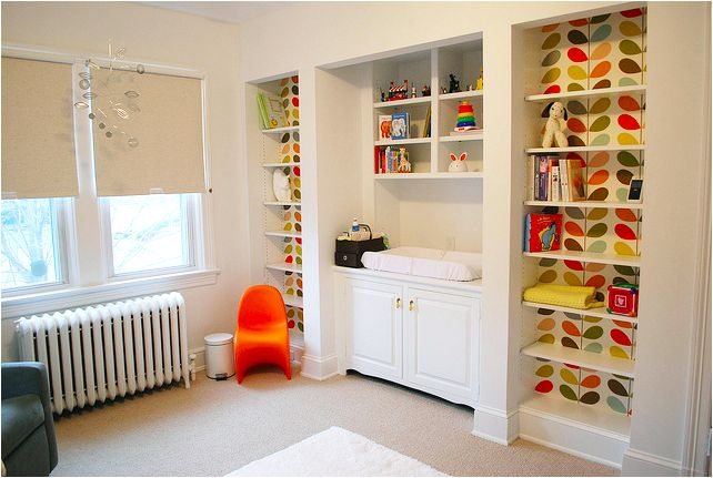 Orla Kiely stem wallpaper in the built-in bookcases, orange child's panton chair, grey glider from monte