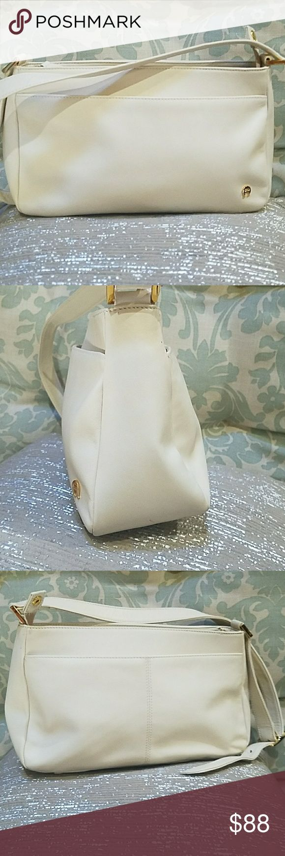 """Etienne Aigner signature cream shoulder bag Etienne Aigner signature cream shoulder bag with three sections of interior and smaller pockets within those, two large outside pockets one on each side. In exceptional condition except for a couple of tiny spots on the strap ad seen in pic #6 and one on the bottom that is barely visible. Interior pockets are immaculate and leather shows no real wear (other than previously mentioned.) Measures 12x3.5x7"""" Etienne Aigner Bags Shoulder Bags"""