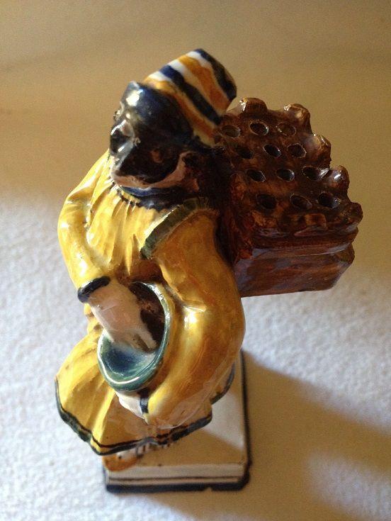 Piccola scultura porta stecchini, Este, manifattura Franchini, XIX secolo, Terraglia dipinta con smalti policromi, Museo Giuseppe Gianetti, Saronno ------------ Sul volto porta una maschera nera e il costume può far pensare ad un Pulcinella, rappresentato con il secchio di spaghetti sottobraccio. Il contenitore portato a spalle mostra tanti fori con la funzione di portastecchini. #commedia #maschera #carnevale