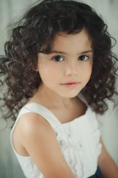 Beautiful little girl with big, dark eyes & pretty curly hair.
