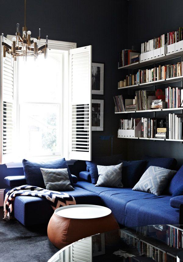 dark walls, bright window, blue chesterfield