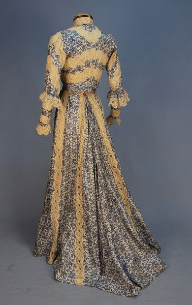 PRINTED SILK HIGH NECK GOWN, c. 1902. 2-piece with blue and white abstract printed and tucked silk panels with bands of scrolling floral cream lace, boned long sleeve bodice with ruffle at elbow, slightly trained skirt, lined in cream silk with hem ruffle.