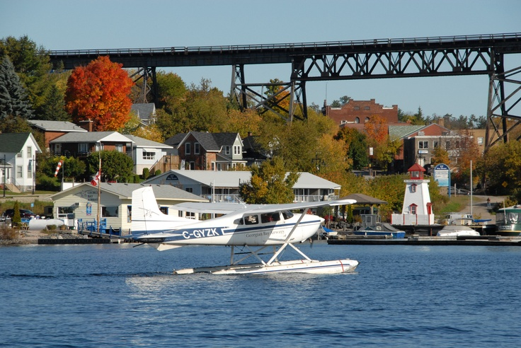 Seaplane taxis Parry Sound Harbour with beautiful red tree in background