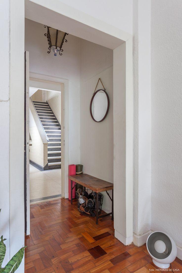 Hall de entrada tem banco de madeira e ferro para calçar os sapatos e espelho redondo.