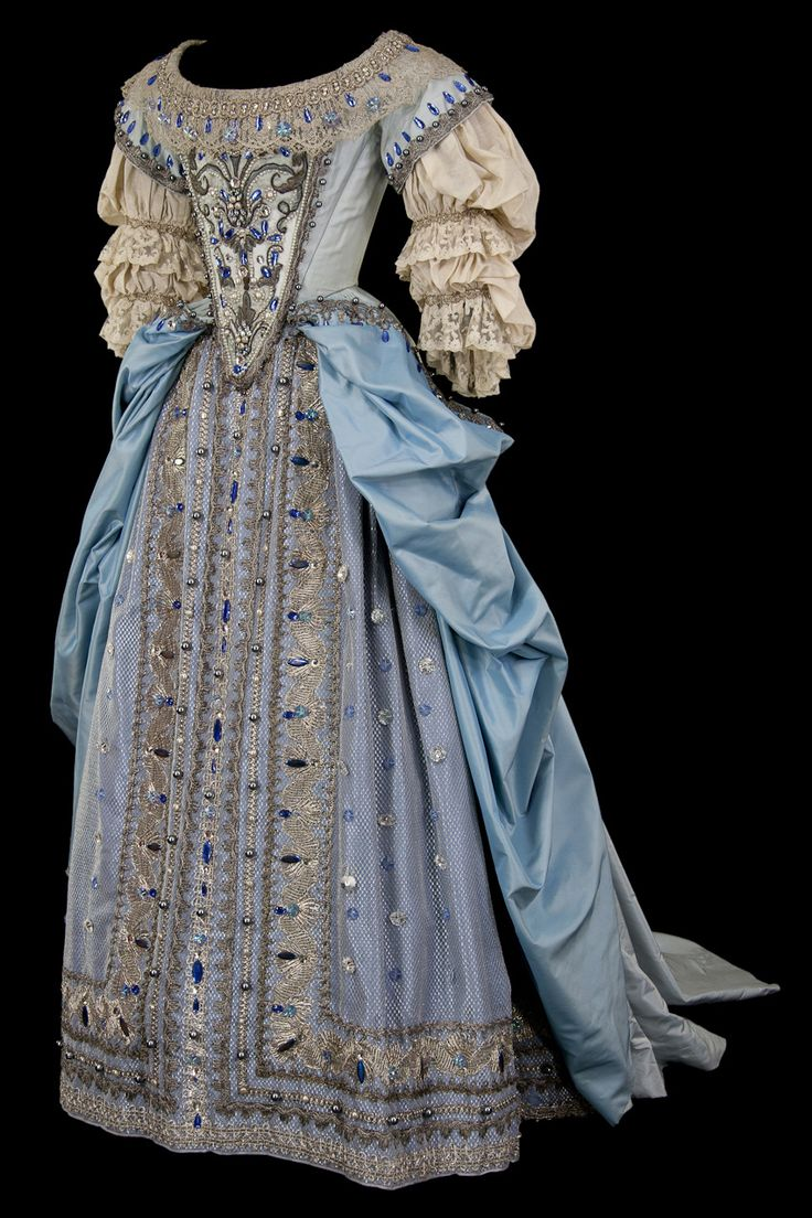 Gorgeous Baroque gown in rich blue.  Embroidered stomacher, Classic wide, round neckline.  The sleeves are gathers at the elbows and wrists, and accented with lace.  The overskirt is pulled back and falls away into a short train.  The underskirt is gathered at the waist, and heavily embroidered & trimmed