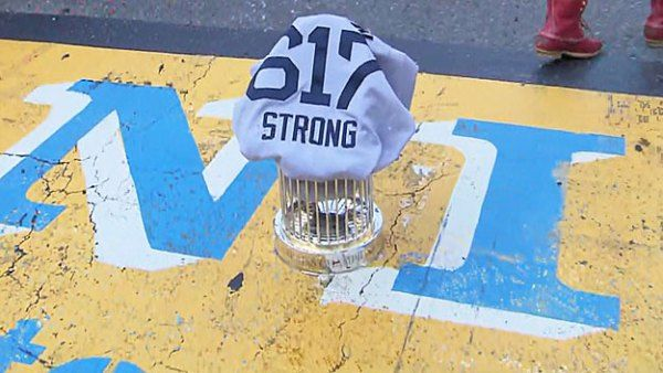 The Red Sox 617 Boston Strong jersey covers the World Series trophy at the Boston Marathon finish line. (WBZ-TV)