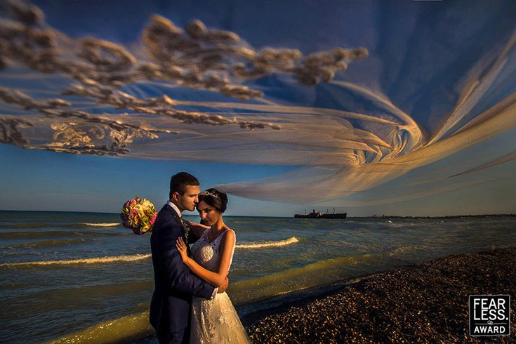 Veils in the wind have become a common prop in wedding photography—but rarely is the effect executed so inventively. Spanning the frame, the embroidered details become delicate clouds in the evening sky. The pebble-strewn beach and ship in the background add a gritty edge to this painterly portrait.