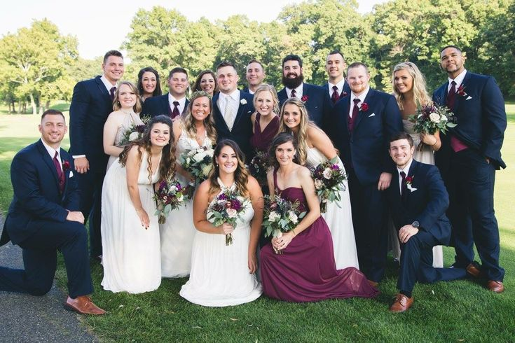 Bridal party on golf course with navy tuxes and bridesmaids in wine, biscotti, and ivory dresses.