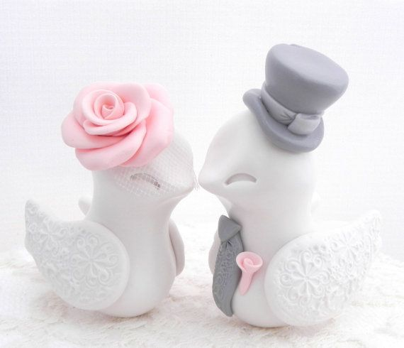 Love Birds Wedding Cake Topper, White, Vintage Pink and Grey, Bride and Groom Keepsake, Fully Customizable. These beautiful Love Birds will add a whole lot of cuteness to your beautiful cake! Simple, elegant and irresistibly cute! She has beautifully sculpted rose on a birdcage veil, and he has an adorable little bow tie and a cute Lincoln hat. Their wings have a beautifully impressed lace design. I can make yours without the hat or with a different hat. Just let me know.