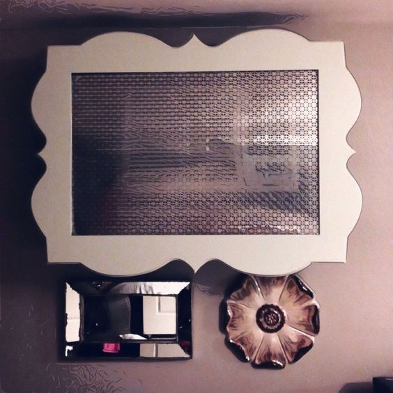 Hide your wall a/c unit by converting a picture frame large enough to cover the unit, staple a mesh cover, add some pieces of wood or legs on each corner to extend away from wall & unit, and then mount to wall.