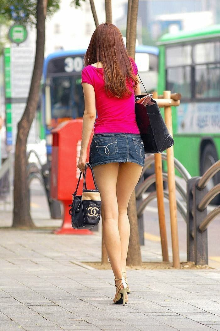Fashion model in blue short skirt with long legs on the street Handsome attractive girl wearing short skirt and high heels standing outside in urban scene. Fashion model in blue short skirt with long legs on the street Woman wearing high heels shoes and short skirt sitting in office chair.