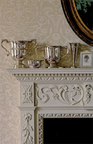 Fireplace off-white & The 'Silvergate' damask paper from Farrow & Ball repeats swirls of classical decoration in the mantel; the look is serene rather than busy because of the neutral colors and similar tones.