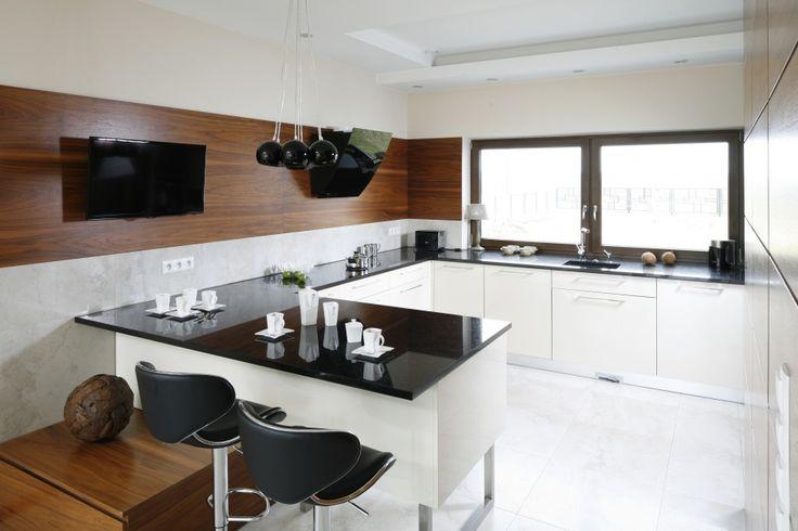 Przestronną kuchnię urządzono w czystej bieli, która ociepla drewno, a dokładnie fornir w wybarwieniu orzecha amerykańskiego. Projekt Piotr Stanisz. Fot. Bartosz Jarosz.