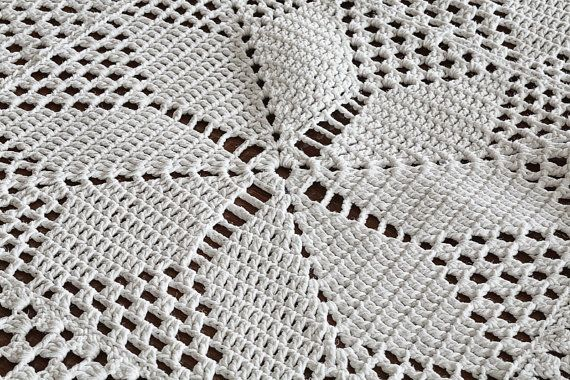 This is a wonderful vintage hand crocheted milk white tablecloth or throw for the sofa or your bed. The pattern is a medieval cross with a scalloped border and the yarn is cotton. There is one very, very faint stain with a break in the thread, otherwise this piece is in excellent vintage condition. I have given it a light wash by hand to freshen and then air dried. Dimensions: 44 x 52 (111.76 cm x 132.08)  ***Most vintage items tend to have a patina from age or some wear from handling, use…
