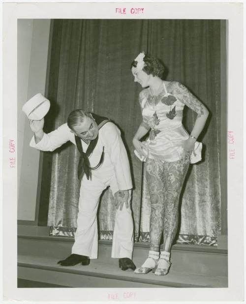 Tattooed lady from the New York World's Fair midway, with an admirer. 1939-1940.