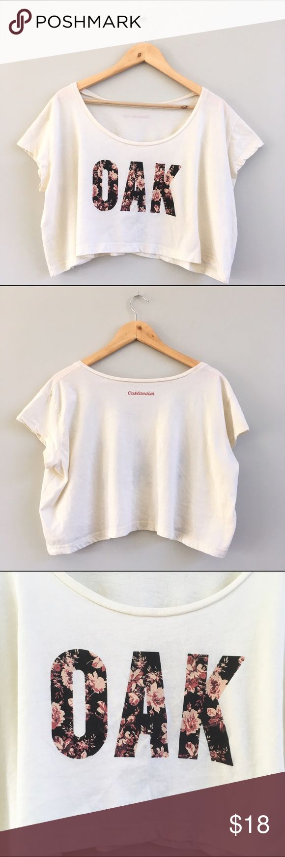 Oaklandish OAK Crop Top Channel your west coast street style with this cream crop top from Oaklandish. Rep Oakland with bold floral print logo! Tag says one size, but fits like a large. Bust: 24in, shoulder to hem: 16in, cotton/polyester blend. Gently worn, great condition. Tops Crop Tops