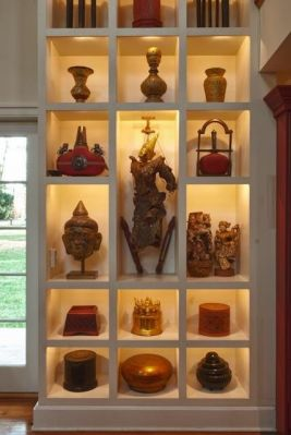 Custom-built boxes display lacquer pieces from Burma and China as well as 19th century Indian water bottles, a Burmese puppet and a Thai Buddha head.
