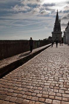 """""""La Rue sur Les Murs"""". Elle est la seule section du rempart médiéval qui a été épargnée de la destruction par Richelieu, qui y voyait un moyen de défense efficace contre les offensives anglaises. À cette époque, la mer venait jusqu'à cet endroit et léchait le pied du rempart, noyant ce qui est aujourd'hui devenu l'Esplanade Saint-Jean d'Acre, qui accueille un grand parking, théâtre chaque année des Francofolies. C.B."""