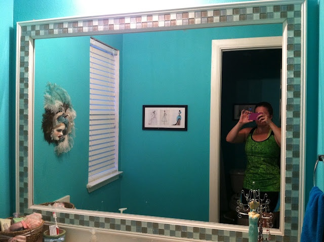 Framing out a bathroom mirror DIY. First, that mirror frame is adorable. Second, I LOVE the wall color!