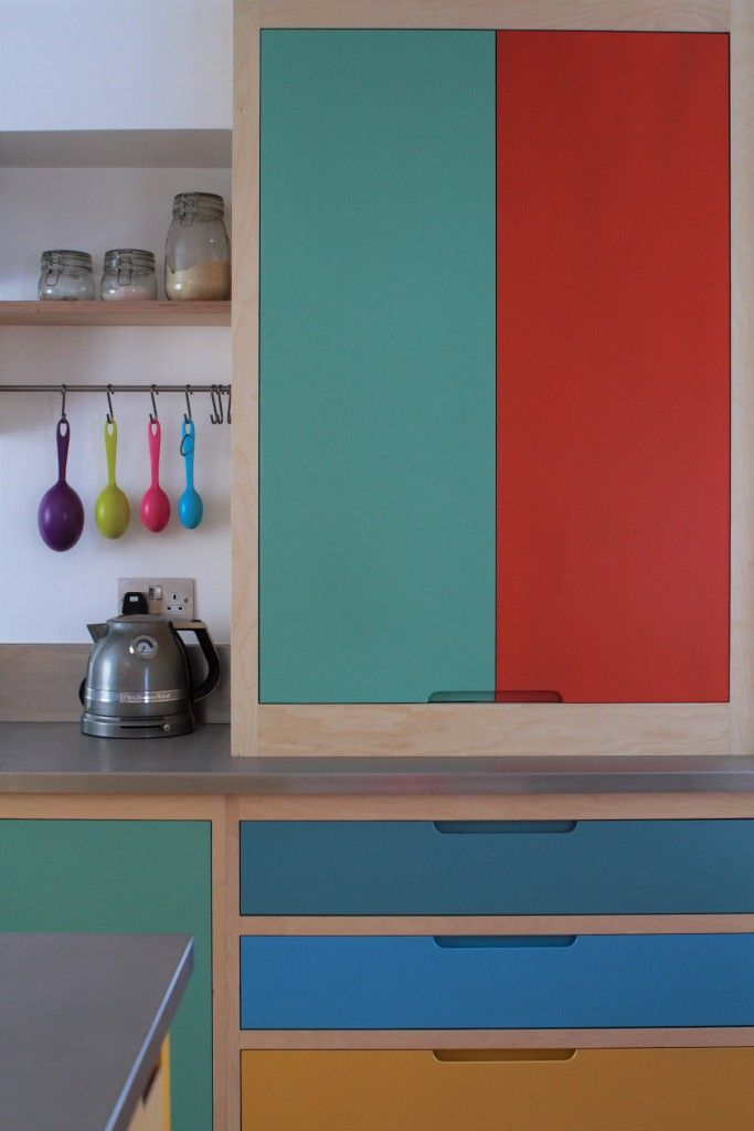 Bright colourful flat panelled plywood cabinets with routed pulls painted with Farrow & Ball colours. Exposed plywood frames contrast the block colour which is topped with stainless steel worktops. The half larder is painted in Arsenic and Charlotte's Lock. The drawers are painted in Babouche, St Giles Blue, and Stone Blue. Also visible is an exposed oak shelf with hanging rail.