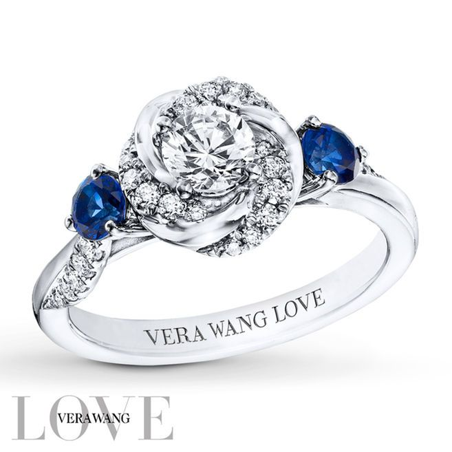 From the Vera Wang LOVE collection, this exhilarating engagement ring showcases round diamonds and 14K white gold swirls from the central diamond. A round sapphire and twinkling diamonds adorn the band on each side. Set into the bezel are two princess-cut sapphires, the signature of the collection and a symbol of faithfulness and everlasting love. The ring has a total diamond weight of 5/8 carat. Diamond Total Carat Weight may range from .58 - .68 carats.