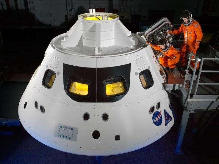 NASA astronauts Cady Coleman and Ricky Arnold step into the Orion crew module hatch during a series of spacesuit check tests conducted at the Space Vehicle Mockup Facility at the agency's Johnson Space Center in Houston.