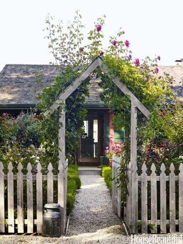 A rose-covered archway frames the front door. Design: Podge Bune.