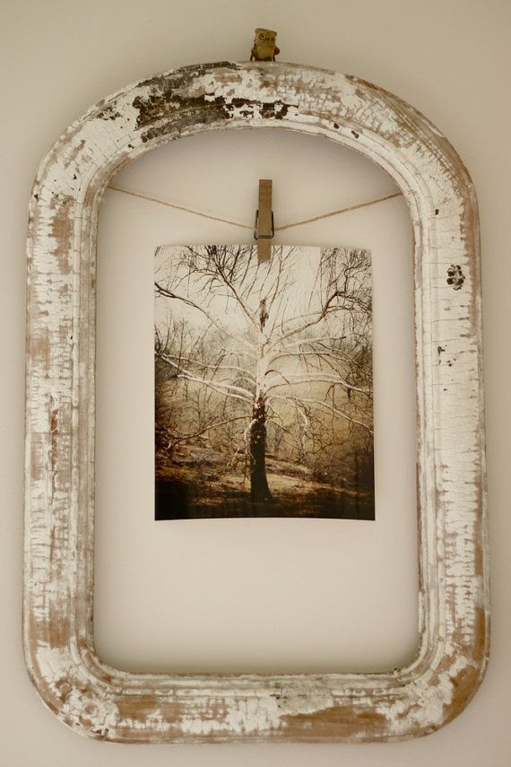 Decorating idea - old photograph hanging from a clothes pin in a shabby frame.
