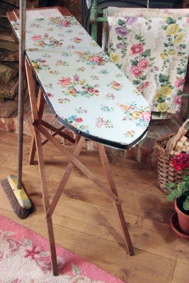I have an old wooden heavy ironing board like this and several flowered covers. I also have two pink hooked rugs that are barely visible in the picture.