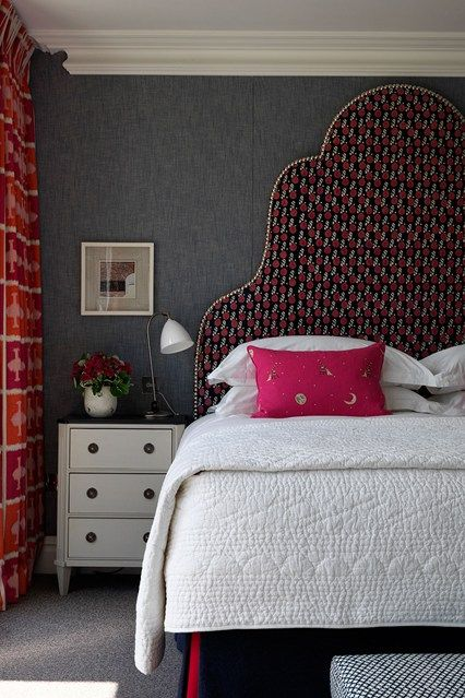 Grey walls with white bedspread and red accents at Ham Yard Hotel in London designed by Kit Kemp
