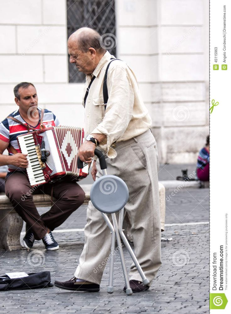 An elderly man with a walking crutch in the city. Behind him, a street artist…