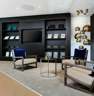 When designing the reception for residential property developer Taylor Wimpey Central London, we wanted to create the sense that clients were being welcomed into an oversized luxury living room. We reflected the high-quality finishes of the client's developments; from plush carpets to beige slipper chairs with luxurious blue velvet cushions.  The living room feel is completed with a dark brown shelving unit that features an integrated flat screen television.