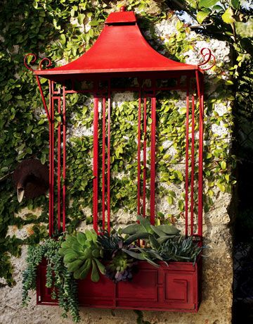 The bright red finish of this Pagoda Wall Planter will heat up any outdoor setting. (315.00) 800-456-7000; horchow.com.