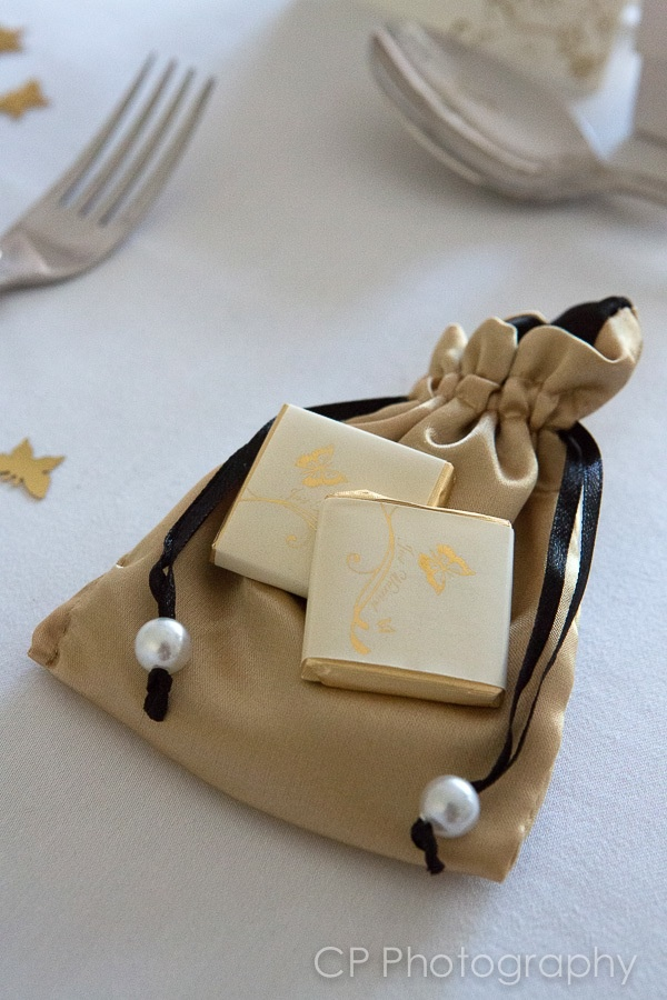 Satin gold favour bag with milk chocolates with printed gold foil chocolate wrappers.  By www.fuschiadesigns.co.uk