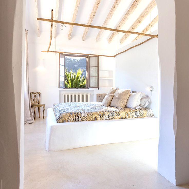White bedroom with neutral bedding and exposed ceiling beams