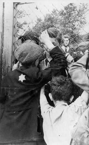 Jewish children bidding farewell from their parents through a chainlink fence, ghetto of Litzmannstadt (Lodz under german occupation, Poland, WWII)