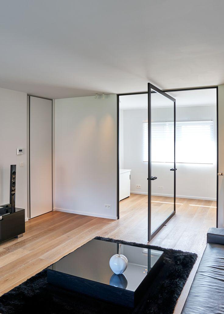 """Grote pivoterende wand tussen living en bureau met daarnaast een strakke """"blokdeur"""" met aluminium omlijsting en verticale randgreep."""