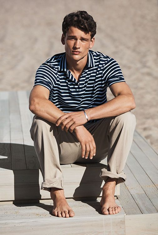 Barefoot man on beach wearing khaki pants & striped Polo shirt