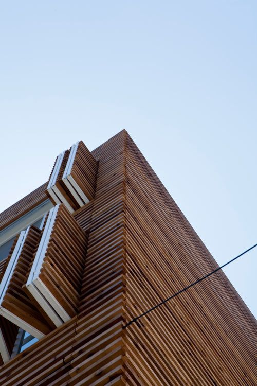 House Covered In Horizontal Slats With Louvered Windows By