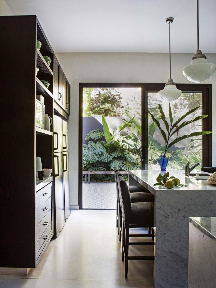 Cocina moderna en la que el mobiliario negro da la nota. En el centro, isla con banquetas tapizadas en gris. Las lámparas colgantes son de La Pasionaria.