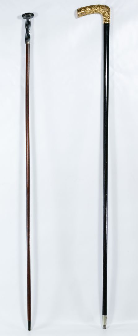 "Lot 431: Cane and Walking Sticks; Two items including a cane with an embossed gold-plate handle marked ""H"" at cuff and a walking stick with a silver-plate handle with cross and floral motif"