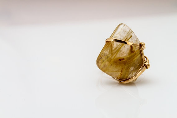 Large Georgia Ring - Congratulations! You're about to make a purchase so unique and special it is quite literally one of a kind.     Sure, we have other gold rutilated quartz rings in our collection, but no one will ever have this particular piece again - trust us we've tried. Every time, the wire seems to take on a life of its own, roughly weaving, wrapping and knotting where it sees fit.     It's a mysterious and sometimes long process, but the final product is well worth it. Don't you…