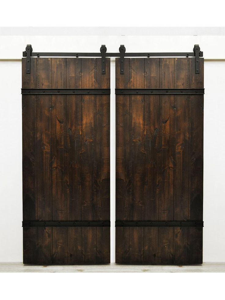 The Drawbridge Barn Door features sturdy lightly distressed wood planks and are bolted together with metal plating. This style is well suited for rustic spaces, but also fits in modern applications. M
