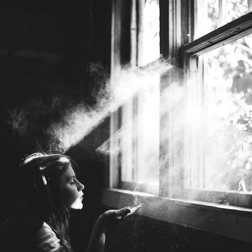 Black and white photography girl at window dust and light make a wish