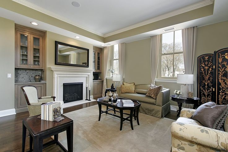 Neutral grey and beige tones surround a rich dark hardwood floor, arched back sofa, and large marble fireplace flanked by natural wood cabinetry in this living room.