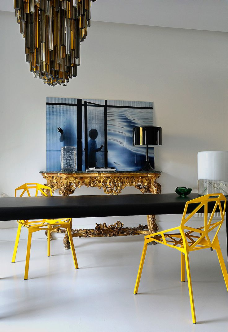 An elaborate gilt console table adds a sense of history to an otherwise modern, minimalist dining space. A contemporary chandelier provides another splash of gold. Modern photography and bright yellow chairs finish the scene.