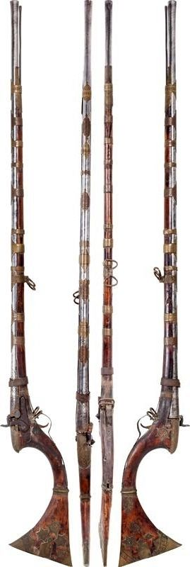 """Indian (Sind) matchlock, 18th century, 19th century percussion conversion, 46"""" flared muzzle barrel with mechanical damask spiral pattern throughout. The thickened breach with incised lattice pattern, probably talismanic. Integral opened sight, wood stock with deeply curved rear and dramatically flared butt the tips sheathed in red pigment inlaid segments with additional plain and matching overlays ahead. The fore stock with chiseled brass bands and cap. Drum conversion with handmade lock."""