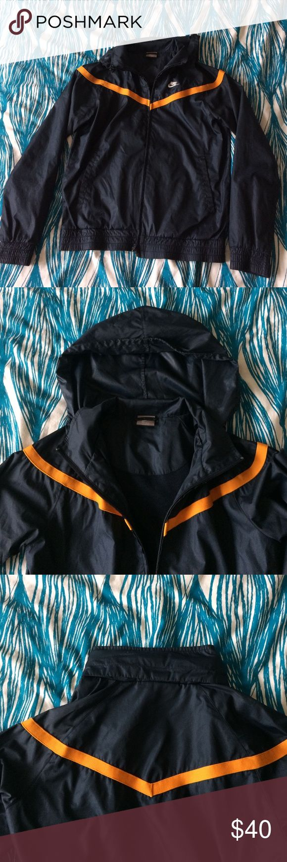 Nike sports jacket size S Navy blue polyester jacket with an orange line detail. The hood can be rolled up and concealed into the collar as seen in the third pic. The jacket has a mesh interior. Works really well in rainy and windy conditions. Very very durable. In great condition! Nike Jackets & Coats Utility Jackets