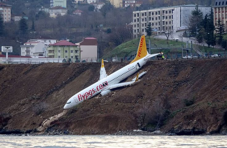 A Pegasus Airlines Boeing 737 passenger plane is seen stuck in mud on an embankment a day after skidding off the airstrip after landing at Trabzon's airport on the Black Sea coast in northern Turkey. (AFP / Getty) https://pow.photos/2018/international-pow-16-22-january/